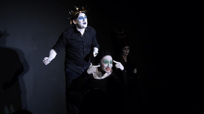 Drei Schauspieler sind im schwarzen Bühnenraum. Sie haben alle drei stark geschminkte Gescihter. Der Mann steht mit einem Lorbeerkranz in der Mitte, links vor ihm steht eine Frau in einer ein wenig gebeugten Halten. Hinten rechts sitzt eine Frau mit hohem Hut.