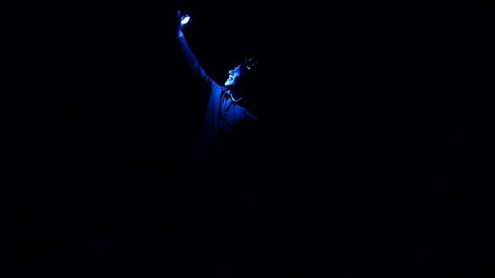 Ein Schauspieler beleuchtet sich im schwarzen Bühnenraum mit einer Taschlampe selber. Er trägt einen Lorbeerkranz