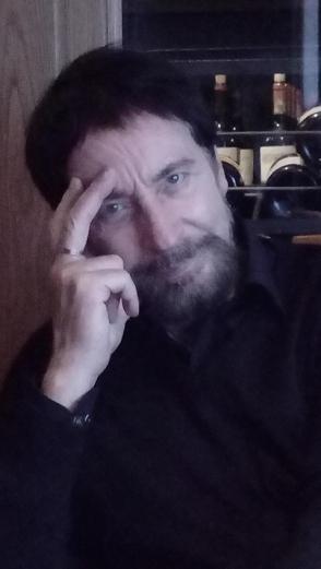 Wolgan Keuter schaut milde lächelnd in die Kamera und stützt sich mit zwei Fingern nachdenklich die Schläfe.