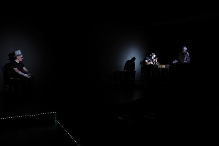 Im schwarzem Bühnenrtaum sitzt links auf dr Bühne ein jüngerer Mann mit graumen Zylinder und grauen Handschuhen. Rechts sitzt an einem Tisch ein Mann mit silberner Maske und graume Hut. Vorne rechts steht eine Frau im weißen Kittel mit einer weißen Haarschutzhaube.