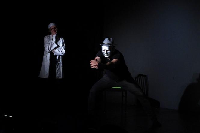 Im schwarzem Bühnenraum steht links eine Frau mit weißem Kittel und weißem Haarnetz. Vorne rechts steht ein Mann mit grauer Maske und graumen Hut und macht eine starke, rührende Gebärde mit beiden Händen.