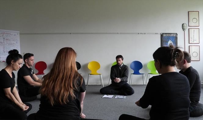 Im Übungsraum sitzt Wolfgang Keuter mit Teilnehmern im Kreis zur Meditation