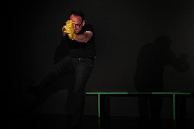 Der Spieler trägt gelde Glitzerhandschuhe auf der schwarzen Bühne