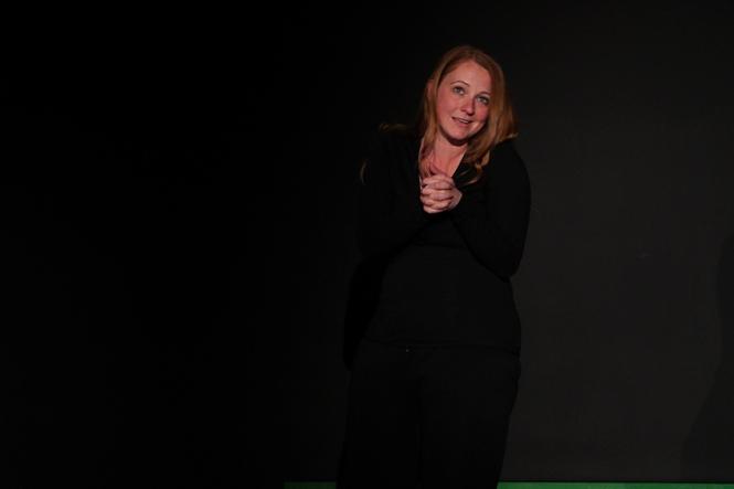 Die Spielerin sitzt mit gefalteten Händen auf einem Stuhl im schwarzen Bühnenraum