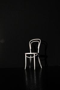 Weisser Stuhl auf der schwarzen Bühne